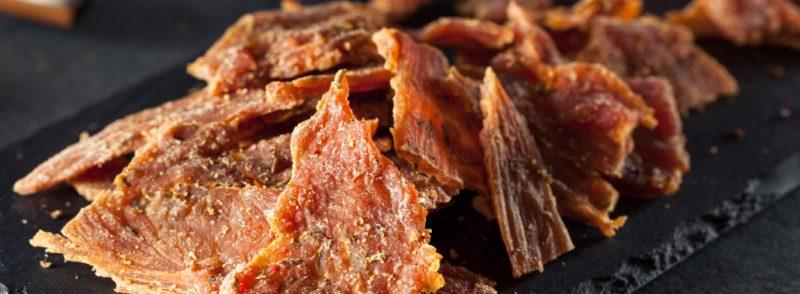 Morceaux de dinde séchée posés sur une assiette en ardoise